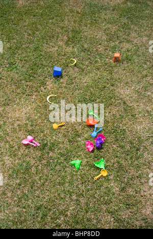 an assortment of brightly coloured kids plastic toys lie scattered on a grass lawn in a private garden - Stock Photo