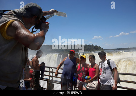 tour group posing for photos on the walkway above the devils throat garganta del diablo iguazu national park argentina - Stock Photo