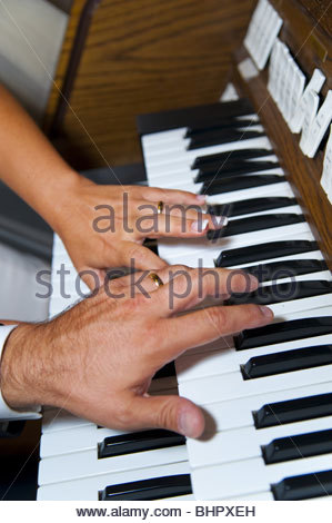 Bride and groom playing piano together - Stock Photo