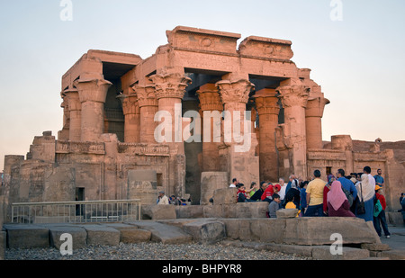 Tourist group listening to guide in front of the double entrance to Kom Ombo temple. - Stock Photo