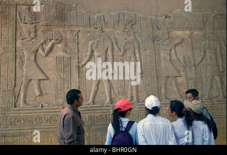 Group of tourists looking at a relief showing the crocodile god Sobek and the falcon god Horus. - Stock Photo