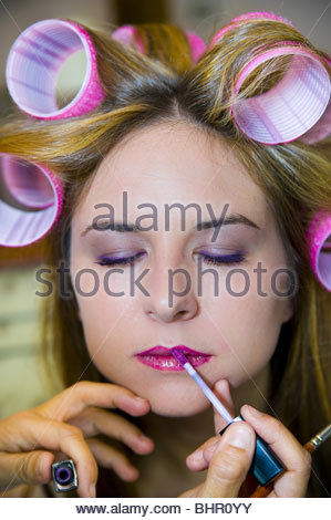 Make-up artist applying lip gloss on a woman with curlers in her hair - Stock Photo