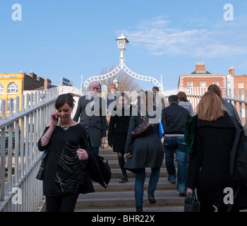 Dublin; Pedestrians crossing famous Ha'Penny or Halfpenny Bridge across the River Liffey in Dublin Ireland - Stock Photo