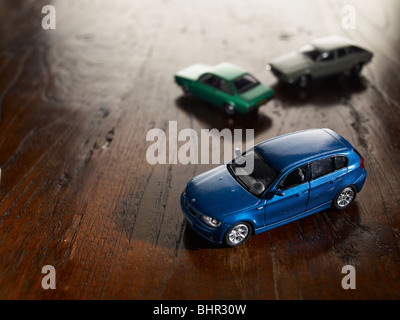 toy cars on a wooden floor car toys play playing - Stock Photo