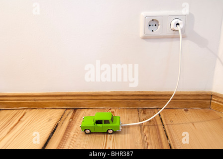 Concept of toy electric car being recharged by plug-in connection to electric supply in the home - Stock Photo