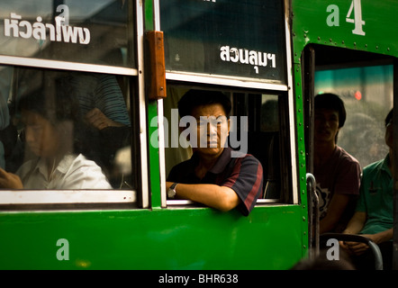 Evening commuter looks out of of bus window in heavy traffic in Bangkok, Thailand - Stock Photo
