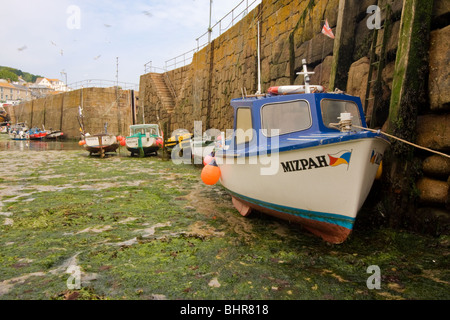 Boats at low tide in Mousehole harbour - Stock Photo