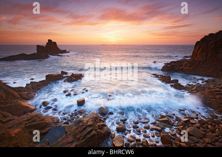 The sun just setting behind Longships lighthouse at the end of a beautiful day as the waves roll into a small bay - Stock Photo
