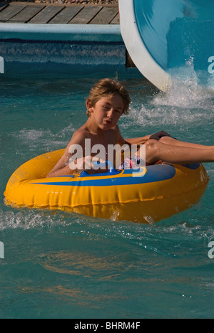 Young boy at a waterpark having fun and has a really excited expression on his face after coming down the waterpark - Stock Photo