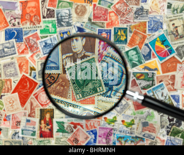 international postage stamps of the world with magnify glass - Stock Photo