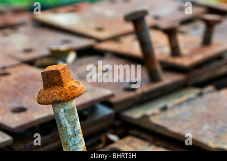 Rusty bolts on a pile of rusting metal plates - Stock Photo