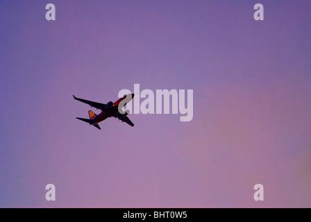 Airliner flying in sunset sky - Stock Photo