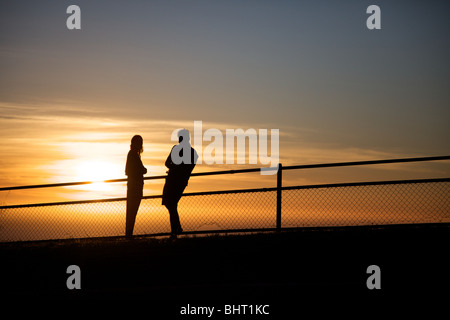 A couple watch the sun set over the Atlantic Ocean in Camps Bay, Cape Town, South Africa.. - Stock Photo