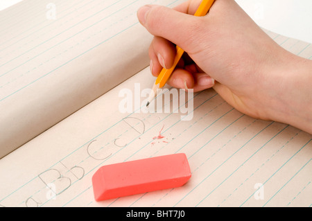 hand on white writing on pad with pencil - Stock Photo