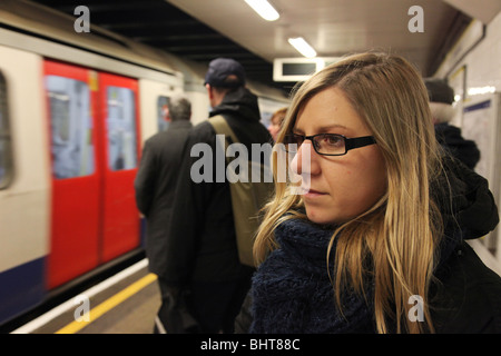 Woman waiting for the underground tube in London - Stock Photo