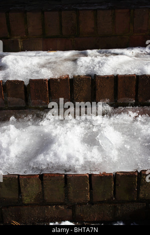 Brick steps covered with snow and ice - Stock Photo