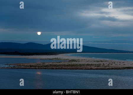 Full moon rising at dusk over mountains, lake, and sea. Location: Mallacoota, East Gippsland, Victoria, Australia - Stock Photo