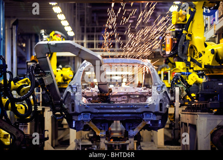 Robots get to work on the body of a new Nissan Motor Co. vehicle at the automaker's assembly plant in Tochigi, Japan - Stock Photo