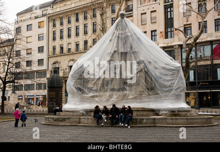 Group of girls and mand sitting in front of a statue wrapped in plastic while it is renovated. Budapest, Hungary - Stock Photo