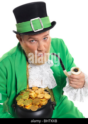 Leprechaun in bright green clothes holding a smoking pipe and pot full of gold - Stock Photo