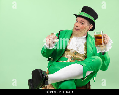 Cheerful Leprechaun in bright green clothes holding a smoking pipe and a beer - Stock Photo