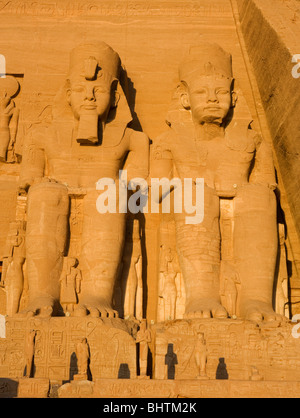 Carved statues of Ramses II Guarding the temple of Abu Simbel at sunrise in Egypt. - Stock Photo