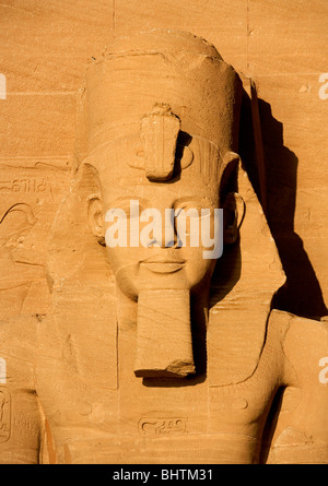 Carved statue of Ramses II head Guarding the great temple of Abu Simbel at sunrise in Egypt. - Stock Photo