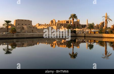 Temple of Karnak reflecting in sacred lake at sunset in Luxor, Egypt. - Stock Photo