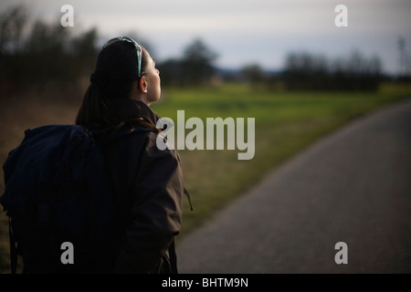 Woman hiker warming her face in late evening winter sun Germany - Stock Photo