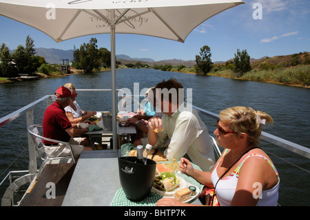 Tourists enjoying lunch aboard boat trip on the Breede River between Worcester and Robertson western Cape South - Stock Photo