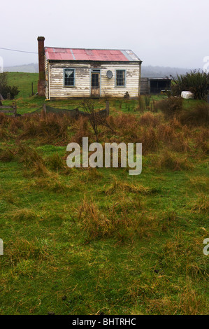 A rundown cottage in isolated countryside with an out of place television satellite dish mounted on wall. - Stock Photo