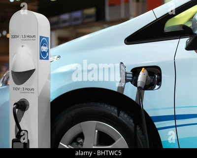 Electric car recharging batteries at a charging station - Stock Photo