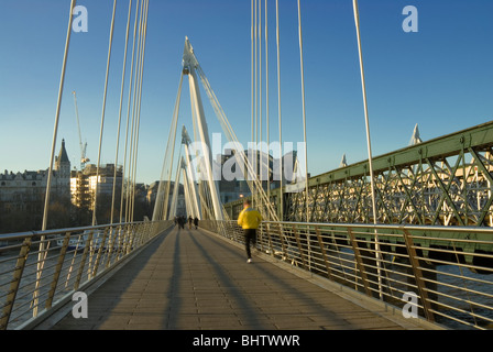 Jogger Running across upstream flank of Golden Jubilee Bridge with Charing Cross Station and the Embankment - Stock Photo