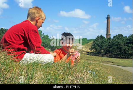 two young boys playing cards in front of the lighthouse on Norderney Island, East Friesland, Lower Saxony, Germany - Stock Photo