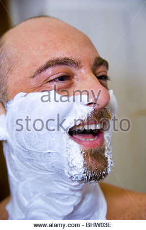 Man laughing with shaving cream on face - Stock Photo