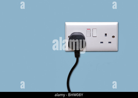 Double electrical power socket and single plug switched on, blue background. - Stock Photo
