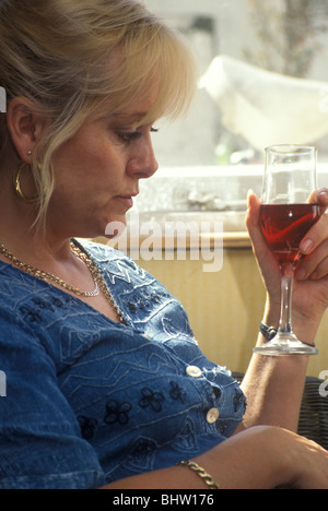 middle-aged woman looking drunk and depressed - Stock Photo
