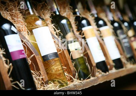 Closeup shot of wineshelf. Bottles lay over straw. - Stock Photo