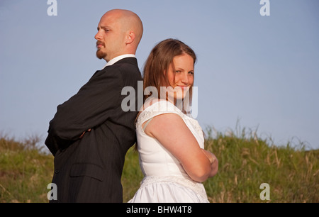 This young Caucasian bridge and groom have their backs towards one another in an argument. Shot outdoors with blue - Stock Photo