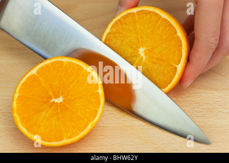 Close up on the hands of a chef slicing a fresh orange in half with a sharp kitchen knife - Stock Photo