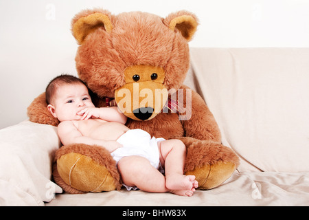Cute Caucasian Hispanic unisex baby in arms of a big brown stuffed teddy bear sitting on couch. - Stock Photo