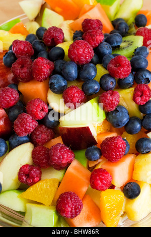Close up of a bowl containing fresh fruit salad of blueberries, raspberries, melon, kiwi, apple, orange and pineapple - Stock Photo