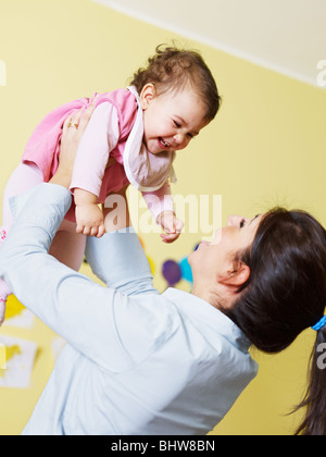 mom lifting her daughter up and smiling. Vertical shape - Stock Photo