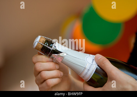 Champagne bottle being uncorked at a party - Stock Photo