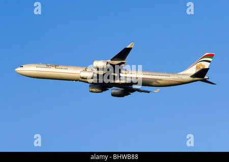 Airbus A340 operated by Etihad Airways climbing out after take off from London Heathrow Airport - Stock Photo