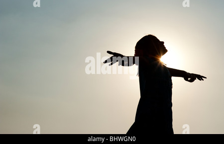 Indian girl silhouette in an unconcerned carefree pose feeling the wind. India - Stock Photo