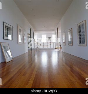 Wooden Flooring In Large Modern White Hall With Group Of Pictures On The Walls
