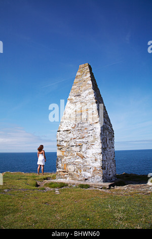 Woman stood looking out to sea next to the coastal beacon at Porthgain, along the Pembrokeshire coastal path in - Stock Photo