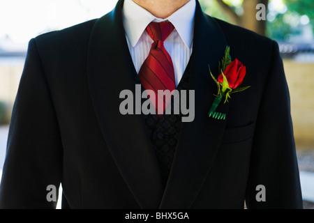 Closeup of a mans suit tie and suit jacket with a rose boutonnière. - Stock Photo