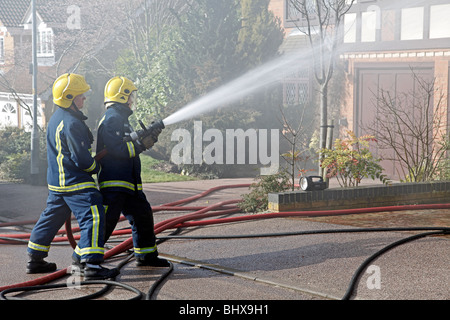 A domestic fire in a suburban neighbourhood in England, with fire fighters dealing with smoke and damage to property - Stock Photo